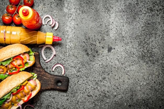 길거리 음식. 시골 풍 테이블에 야채와 허브 핫도그.