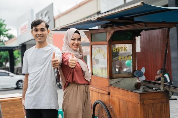 Продавец уличной еды с киоском, где готовят индонезийский куриный сатай на горячем угольном гриле