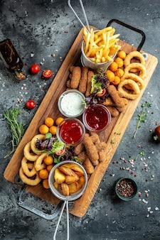 모짜렐라 스틱, 닭 날개, 양파 링, 감자 튀김 및 딥을 곁들인 길거리 음식. 펍 전채, 세로 이미지입니다. 평면도,