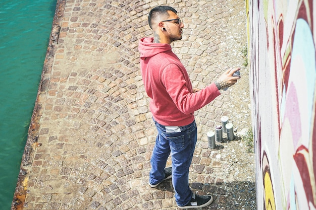 컬러 스프레이로 거리 낙서 예술가는 벽에 낙서 벽화를 할 수 있습니다