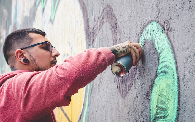 Street graffiti artist painting with a color spray can
