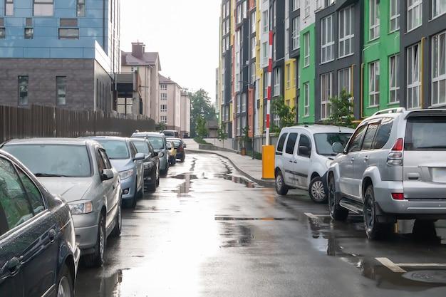 雨天時に駐車中の車を持っている人がいない街の通り。道路に雨が降る。雨と車。雨の街の通りに駐車した車の背景。対称的な駐車車。