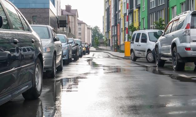 Улица в городе без людей с припаркованными машинами в дождливую погоду. дождь на дороге. дождь и машины. фон припаркованных автомобилей на дождливой городской улице. симметричные припаркованные автомобили.