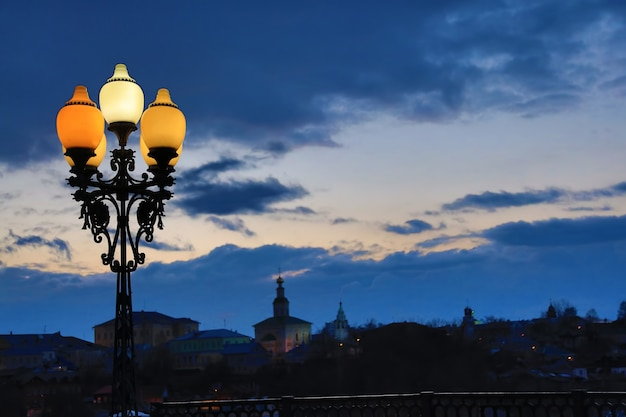 Street lamp on the background of a beautiful sunset sky with clouds colorful houses and church