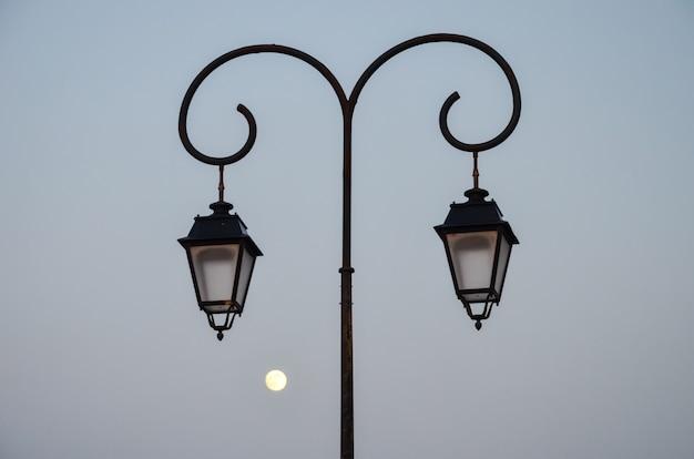 Уличный фонарь вечером на фоне луны на побережье греции (ираклион)
