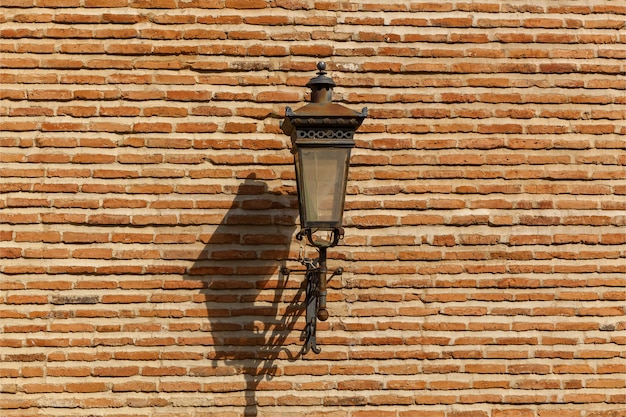 Street lantern on the wall of fence from a stone