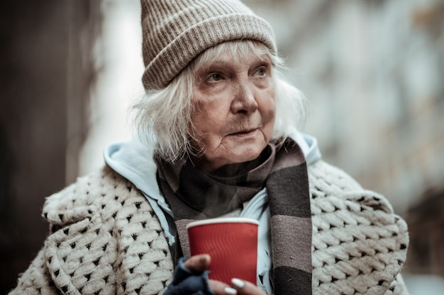 Street life. portrait of an old sad poor woman holding a cup of tea