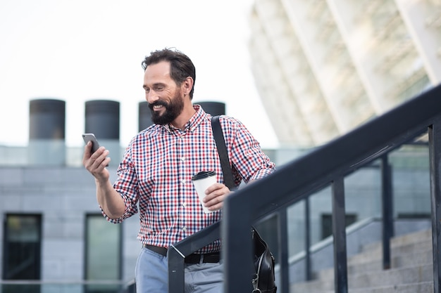 Street lifestyle. cheerful handsome bearded man using his phone while standing outdoors