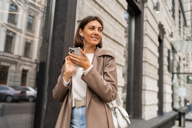 Уличный образ жизни портрет стильной европейской деловой женщины брюнетки в кожаной куртке, позирующей на открытом воздухе
