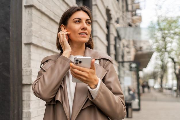 야외 포즈 가죽 코트에 세련 된 유럽 비즈니스 갈색 머리 여자의 거리 라이프 스타일 초상화