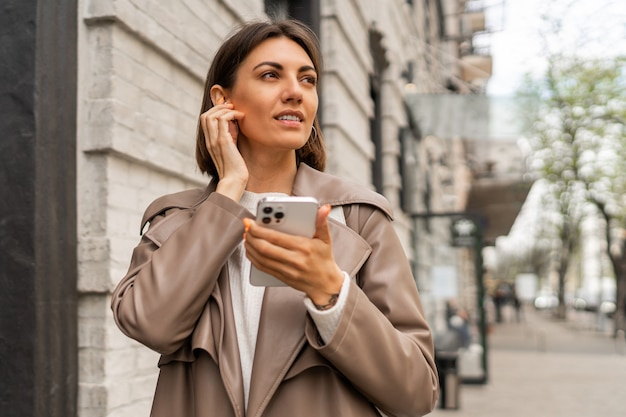 Ritratto di stile di vita di strada di elegante donna bruna di affari europei in cappotto di pelle in posa all'aperto