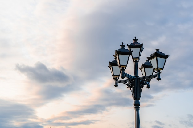 Street light with classic lamppost against a cloudy sky. vintage style lamp post outdoors with copy space