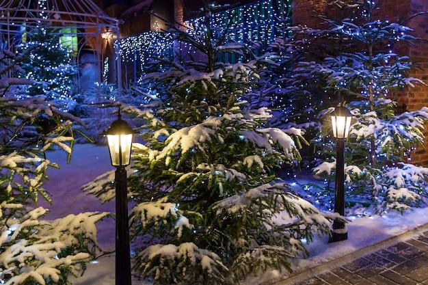 街灯、雪の中のクリスマスツリー、青い花輪がお祭りの雰囲気を醸し出しています。美しい新年の風景、雪の中のクリスマスツリー