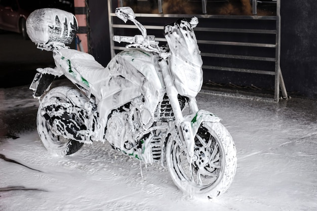 Street motorcycle in soap at the car wash washes