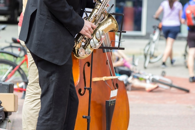Street musician's hands playing saxophone and double-bass in an urban environment