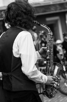 Руки уличного музыканта, играющего на саксофоне в городской среде. черно-белое изображение