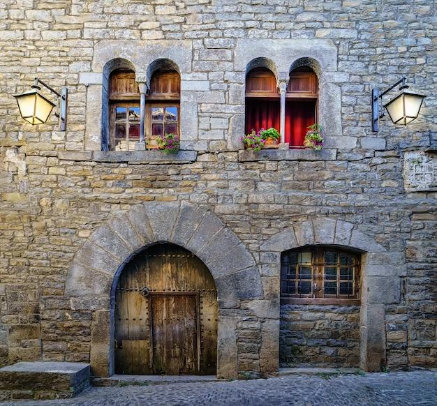 석조 주택과 자갈 바닥, 가로등, 과거의 분위기가있는 오래된 중세 마을의 거리입니다. 스페인, 아 인사,