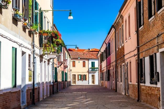 Улица мурано с красочными домами и растениями в венеции, италия.