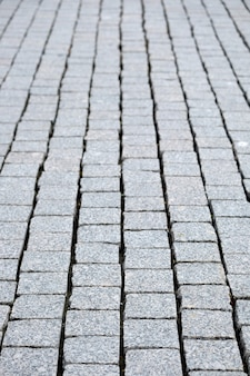 Street paved with gray cobblestones vertical view close-up