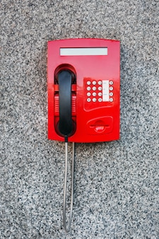 Street pay phone red on the wall.