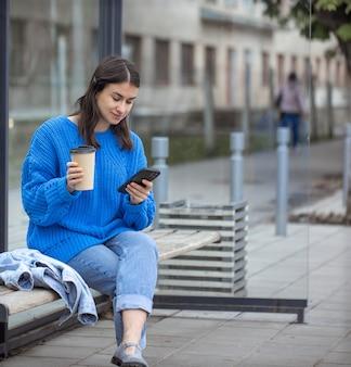 彼女の手に携帯電話と行くコーヒーを持っている若い女性のストリート写真