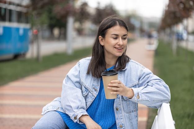 Уличное фото привлекательной молодой женщины, сидящей на скамейке с кофе в руке.