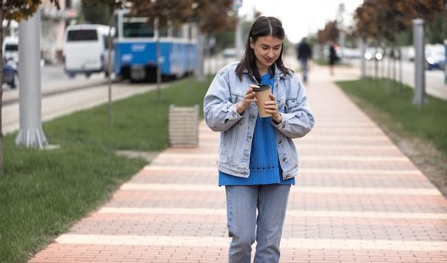 Уличное фото привлекательной молодой женщины, идущей по улице города с кофе в руке.
