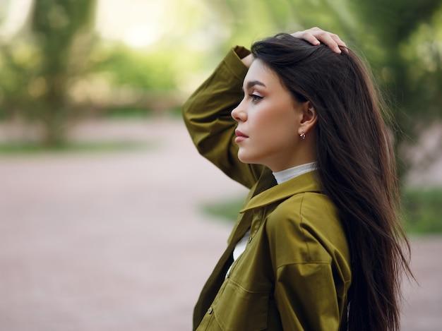 ストリートフォト。公園で屋外でポーズをとる若いスリムなファッションモデル
