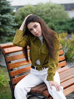 Street photo. young slim fashion model posing outdoors in the park
