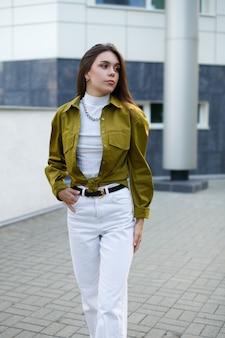 Street photo. young slim fashion model posing outdoors