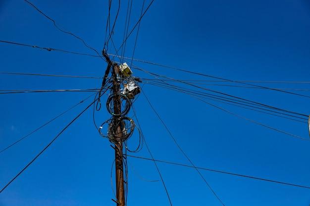 Уличный столб с множеством электрических проводов и оптоволоконных кабелей, оптоволоконный кабель на фоне голубого неба.