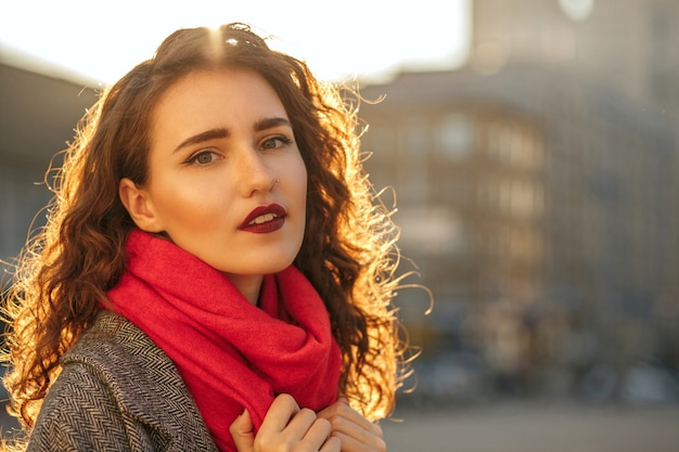 Street portrait of attractive brunette lady with red lips walking down the city in sunny evening. space for text