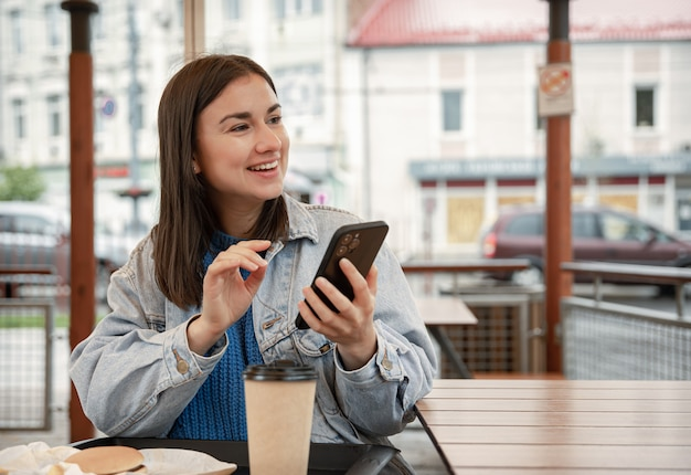 Ritratto di strada di una giovane donna allegra su una terrazza di un caffè, con in mano un telefono.