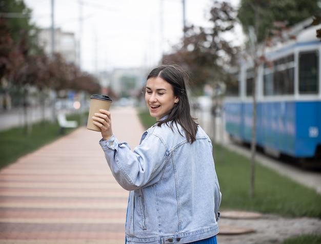 Ritratto di strada di una giovane donna allegra in una passeggiata con caffè in un parco sfocato.