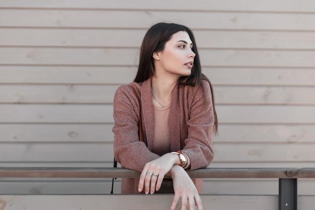 도시에서 빈티지 나무 벽 근처에 아름 다운 머리와 우아한 세련 된 코트에 거리 초상화 아름 다운 좋은 젊은 여자. 트렌디 한 착용감의 멋진 소녀 모델이 서서 야외 난간 근처에서 옆으로 보입니다.