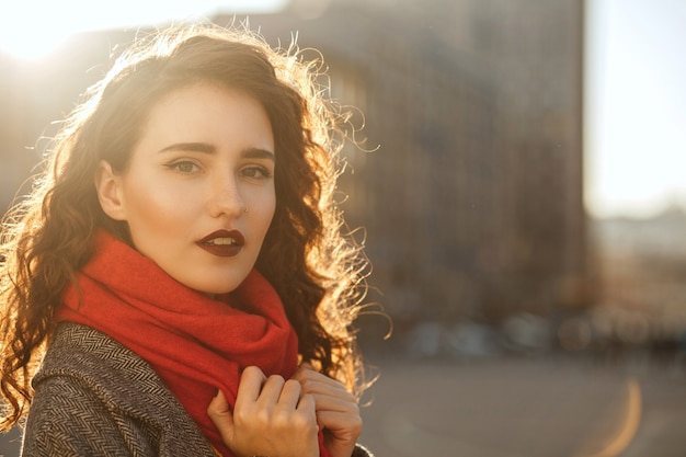 Street portrait of fashionable brunette woman with red lips walking down the city in sunny evening. space for text