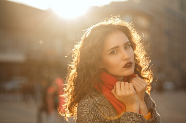 Street portrait of glamor brunette model with red lips walking down the city with sun glare. space for text