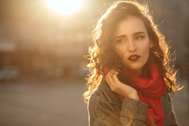 Street portrait of lovely brunette woman with red lips walking down the city with sun glare. space for text