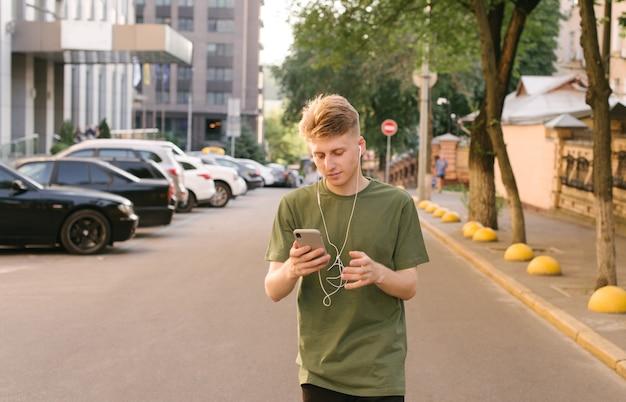 Уличный портрет красивого молодого человека слушает музыку в наушниках и использует смартфон
