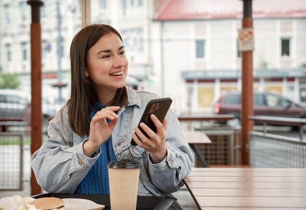 Уличный портрет жизнерадостной молодой женщины на террасе кафе, держащей телефон.