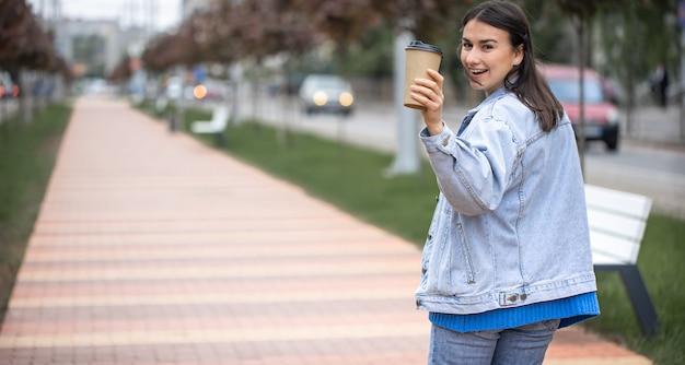 흐리게 공원 복사 공간에 커피와 함께 산책에 쾌활 한 젊은 여자의 거리 초상화.