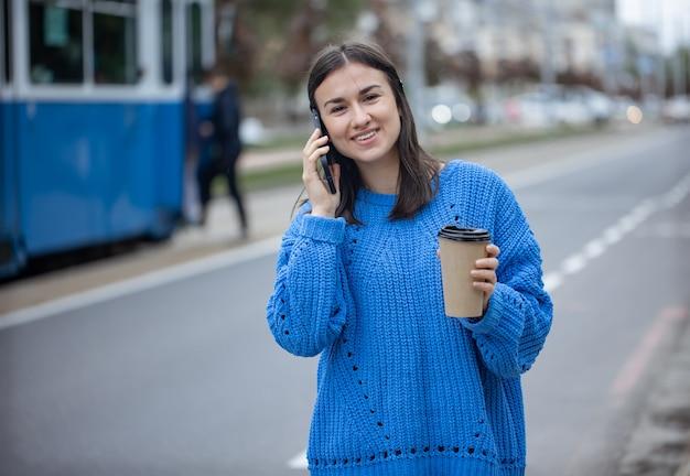 ぼやけた背景に彼女の手にコーヒーと電話で話している陽気な若い女性のストリートポートレート