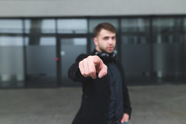 指を示すスーツを着た男のストリートポートレート