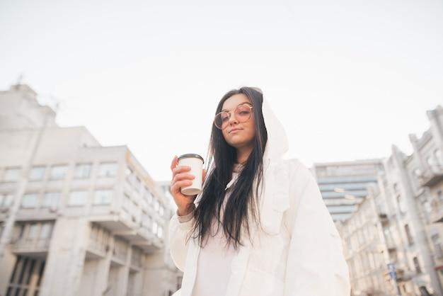 그의 손에 커피 한잔과 함께 거리에 서있는 캐주얼 의류에 세련된 여자의 거리 초상화, 카메라를 찾습니다