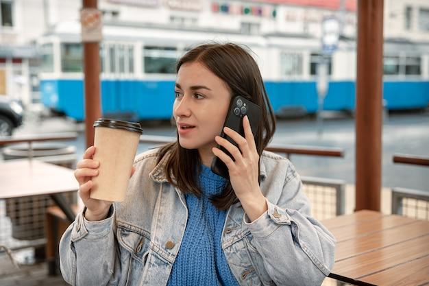 コーヒーを飲み、電話で話し、誰かを待っている若い女性のストリートポートレート。