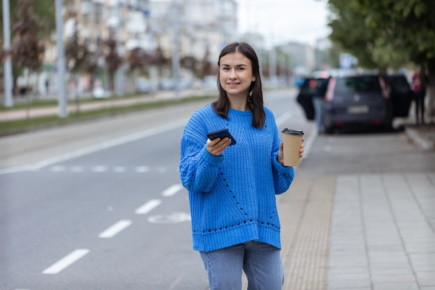 彼女の手に携帯電話と行くコーヒーを持っている若い女性のストリートポートレート