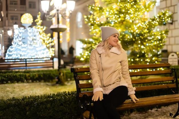축제 크리스마스 박람회에 웃는 아름 다운 젊은 여자의 거리 초상화. 클래식하고 세련된 겨울 니트 옷을 입은 레이디.