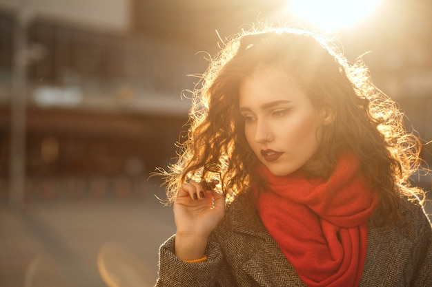 Street portrait of pretty brunette girl with red lips walking down the city in sunny evening. space for text