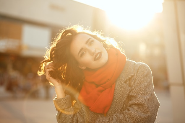 Street portrait of romantic brunette model with red lips walking down the city with sun glare. space for text