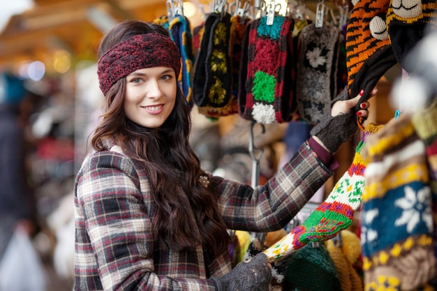 Street portrait of smiling beautiful young woman choosing warm knitted things on the festive christmas fair. travel, tourism, holidays and people concept.